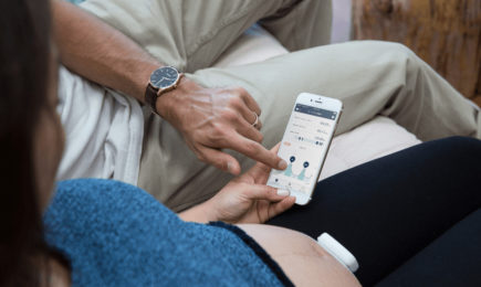 checking Bloomlife app and monitoring contractions with Bloomlife contraction tracker in third trimester of pregnancy for labor and birth